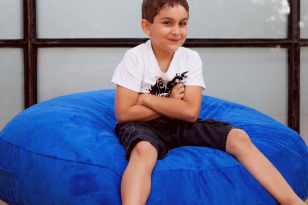 Мальчик сидит на синем бин беге